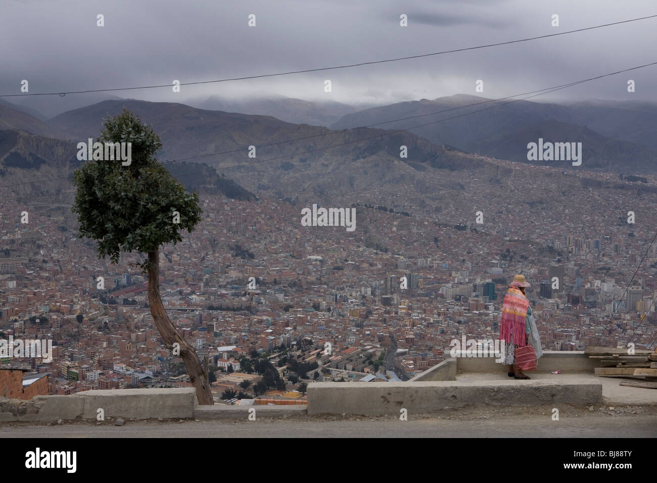 Indigenous woman looking out across la paz as seen from el alto, bolivia - Stock Image