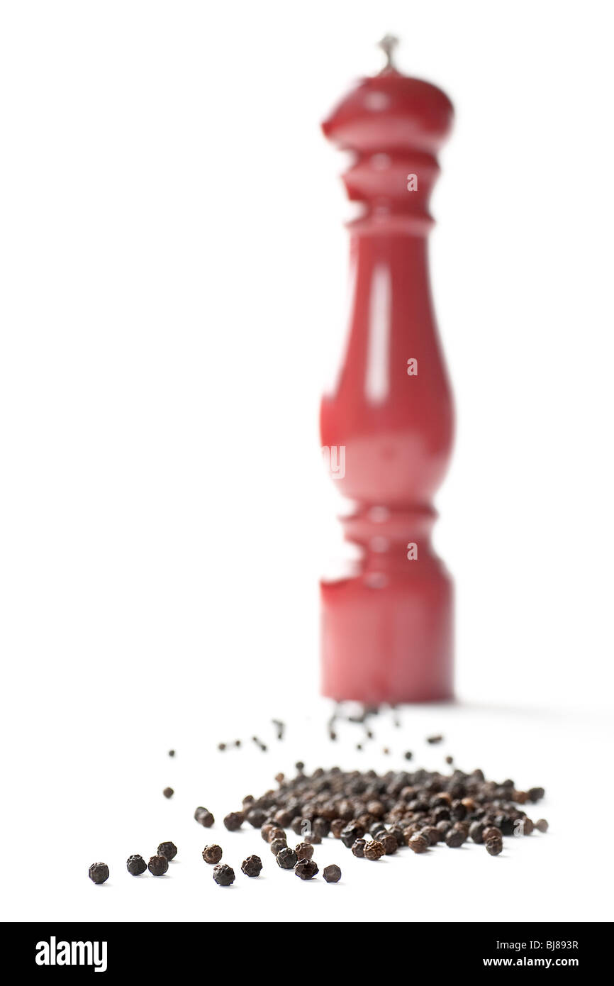 Pepper mill with pepper corns. Shallow focus. Focus on pepper corns. - Stock Image