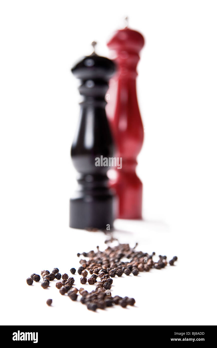 Two pepper mills with peppercorns - Stock Image