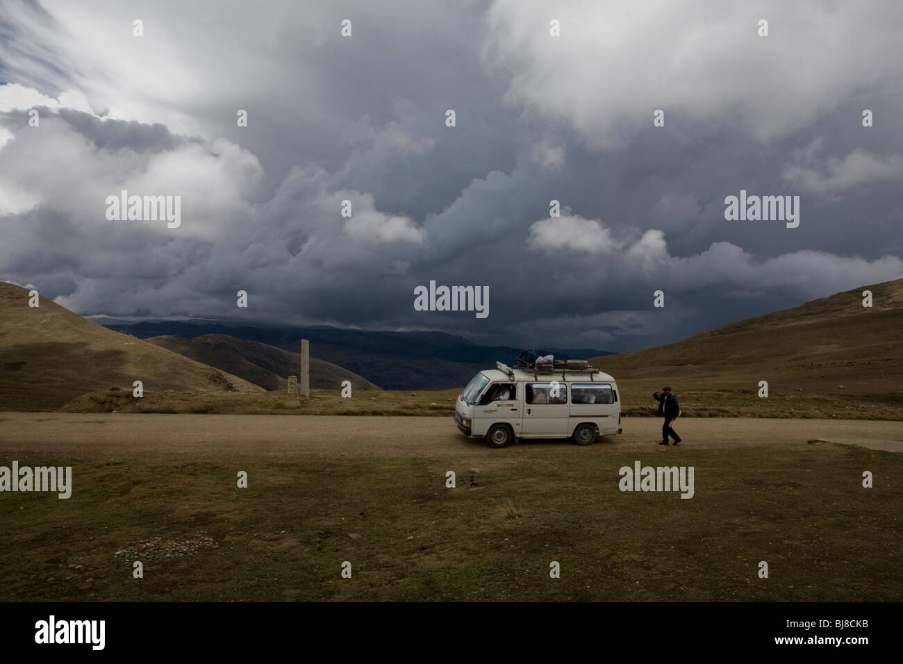 Minivan pit stop in bolivian mountains under dark clouds - Stock Image