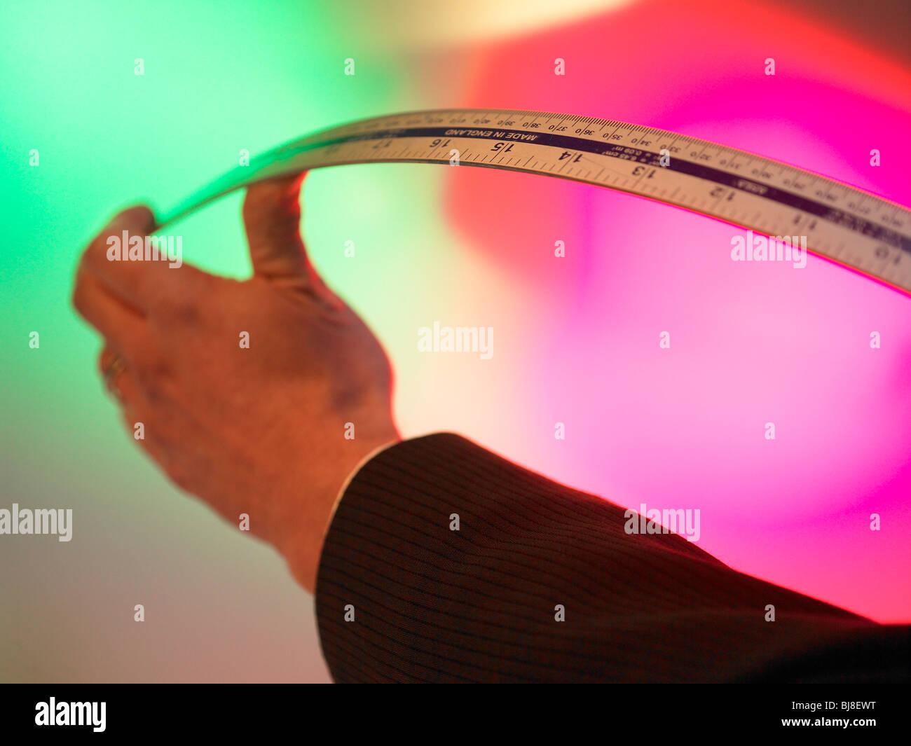 Hand bending a ruler - Stock Image