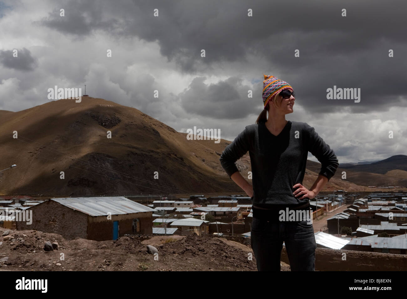 western woman in traditional hat and sunglasses standing in front of peruvian mountain village - Stock Image
