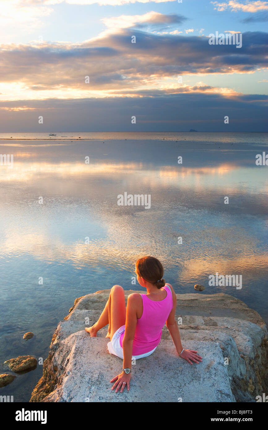 Girl sitting at end of pier looking into sunset Matabungkay; Batangas; Southern Luzon; Philippines - Stock Image