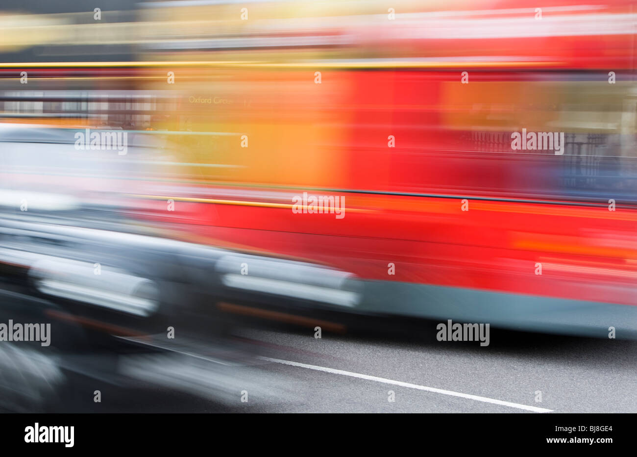 Taxi and Red Double Decker Bus Driving Down Street in London, Blurred Motion, transportation transport black red - Stock Image