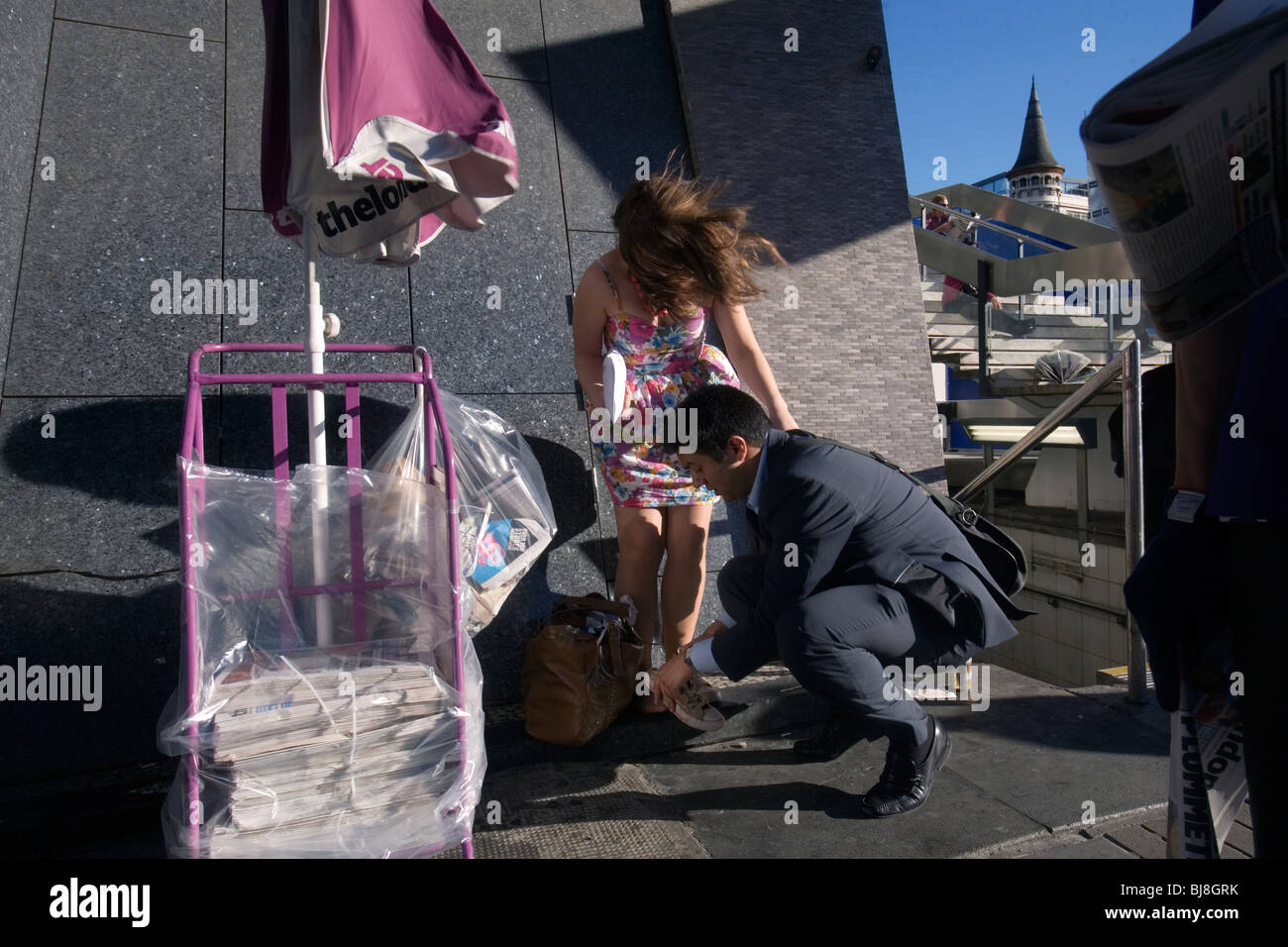 a woman being helped with her shoe in london - Stock Image