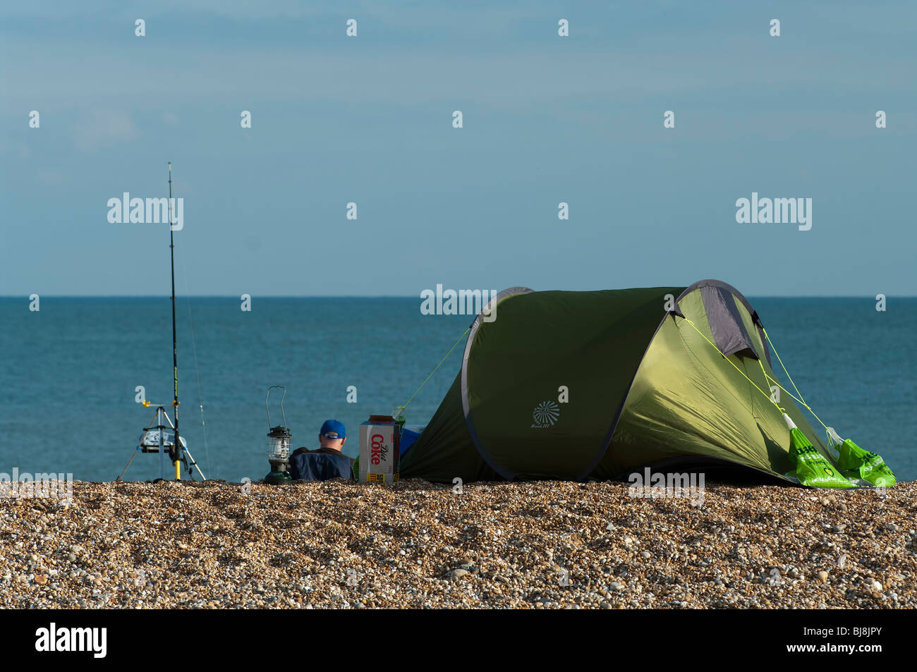 Sea angler waits to catch fish at Dungeness, Kent, England - Stock Image