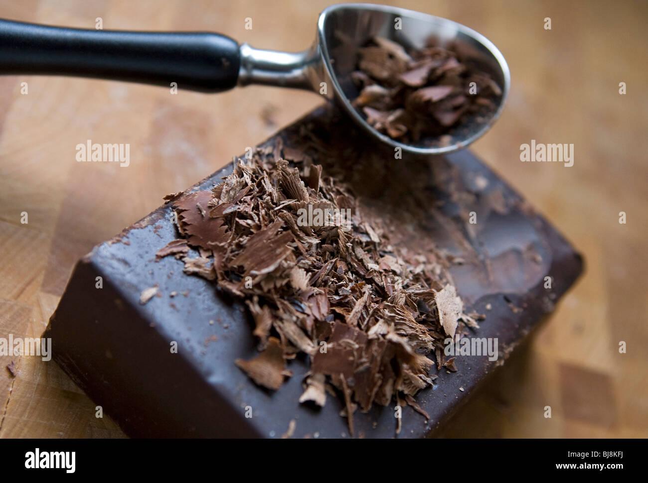 A block of dark chocolate and dark chocolate shavings.  - Stock Image
