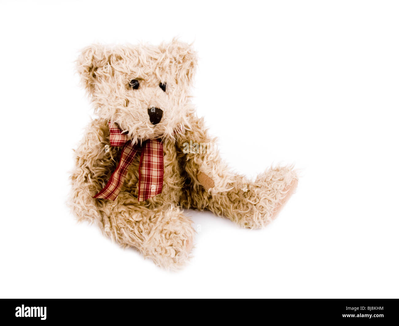Brown teddy-bear with red bow on white background. Stock Photo