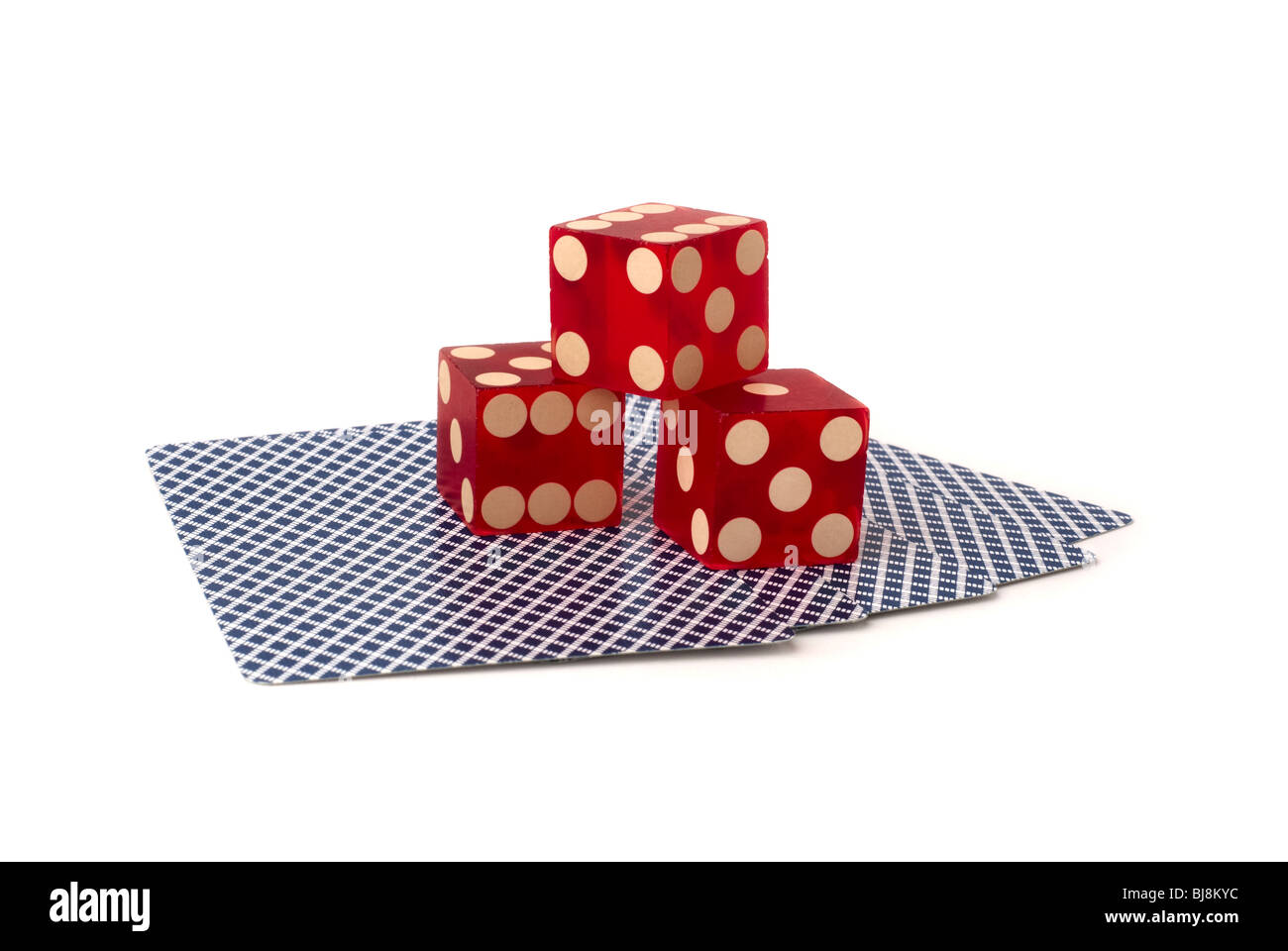 three red dice on five upside down playing cards with blue pattern, shot in studio on white background - Stock Image