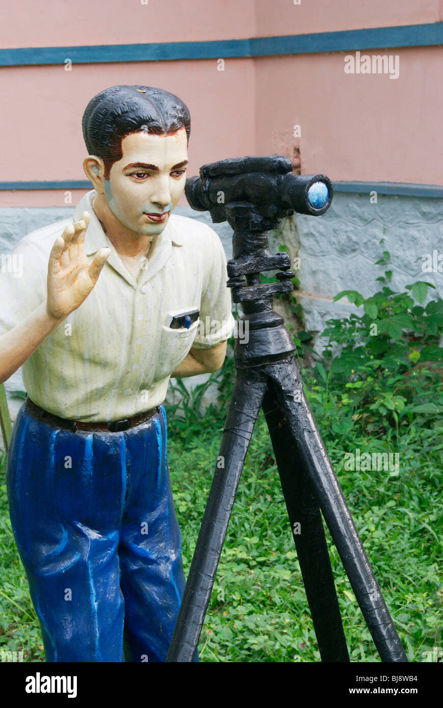 Surveying man sculpture in the beautiful Neyyar Dam garden of Kerala,India.Surveyor Man Statue with Tripod and survey - Stock Image