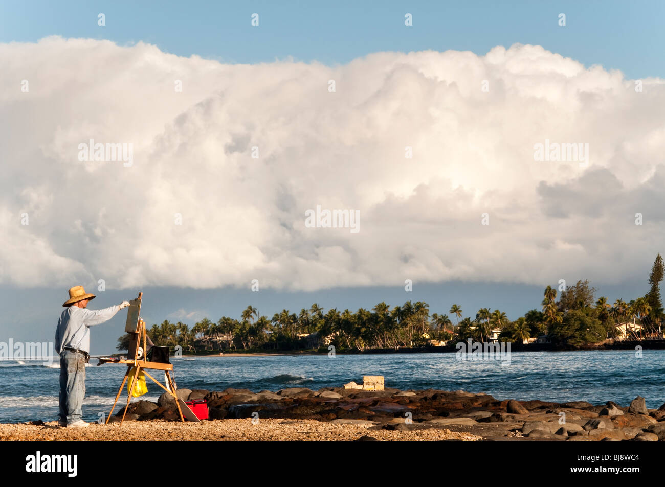 'Plein Air' artist painting at Lahaina Harbor Maui Hawaii.  Giant clouds over Molokai in the background - Stock Image