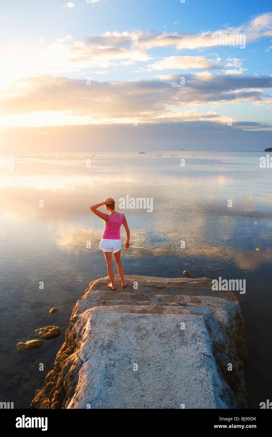 Girl standing at end of pier looking into sunset Matabungkay; Batangas; Southern Luzon; Philippines - Stock Image