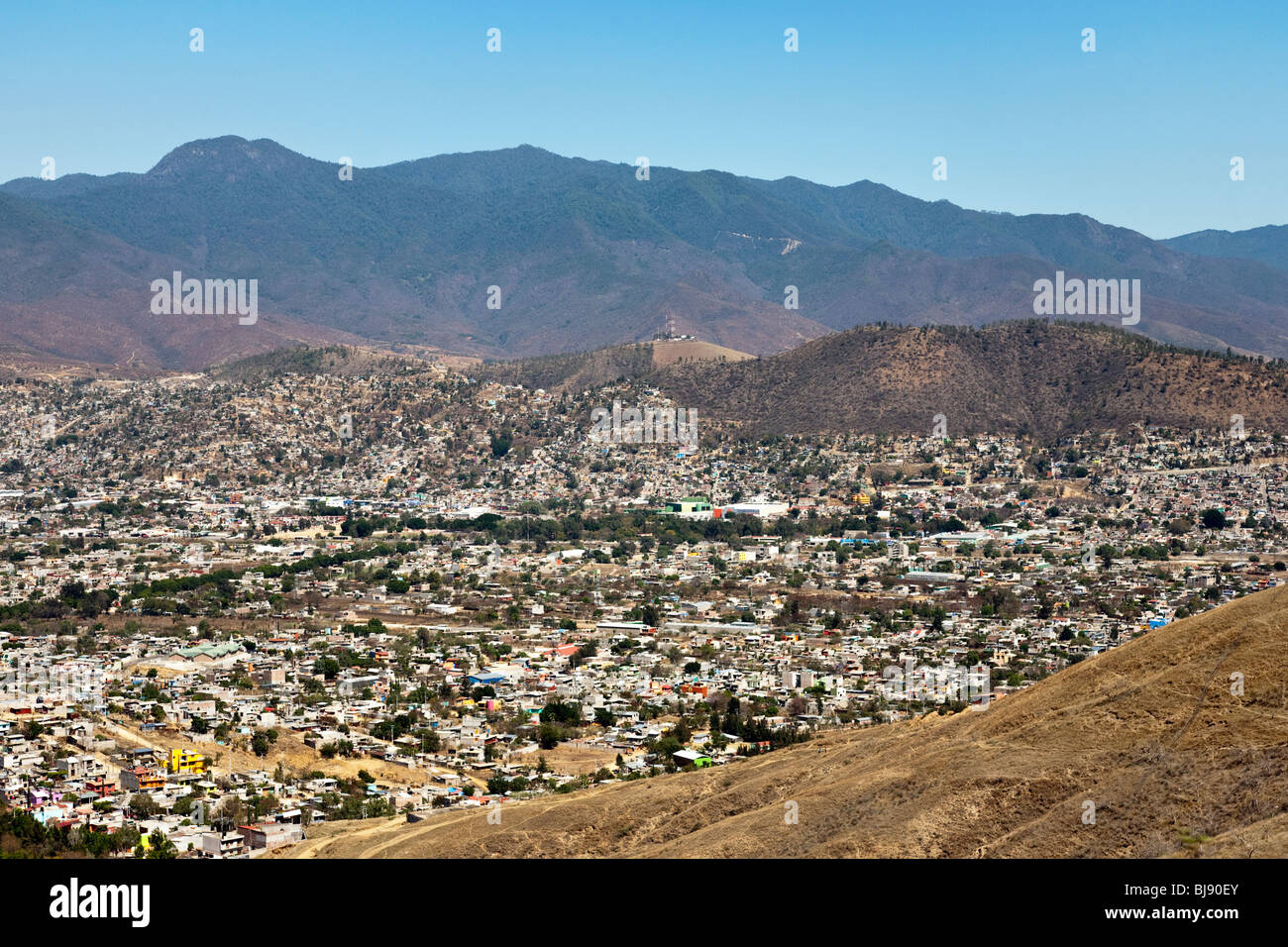view over Oaxaca City outskirts to magnificent mountains & clear blue sky beyond on a beautiful day Oaxaca State - Stock Image