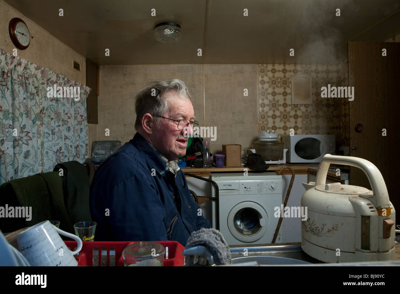 Senior single man watching a kettle boil in his motor home Stock Photo