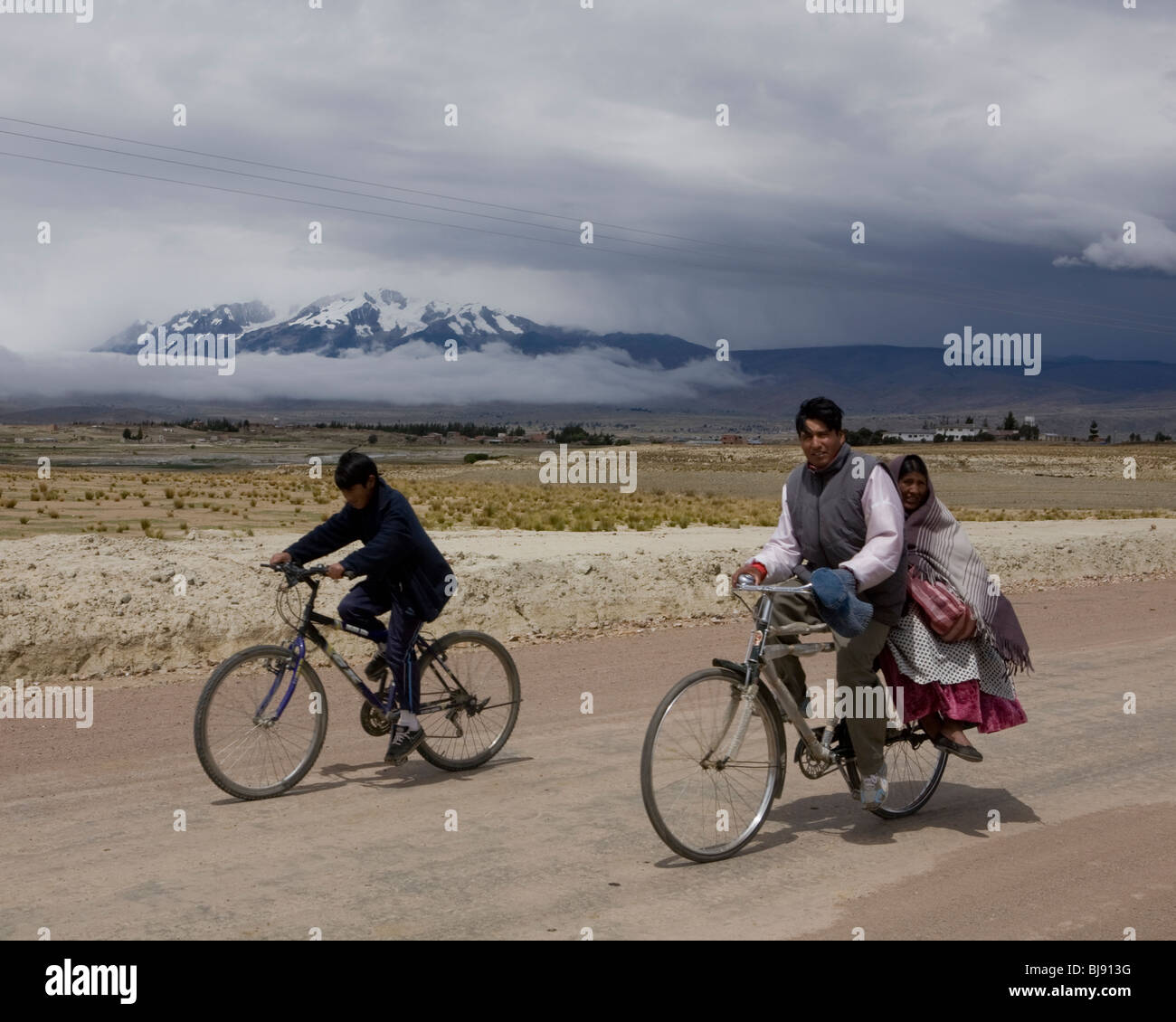 Locals bicycling home in the bolivian countryside with illampu mountain in the background - Stock Image