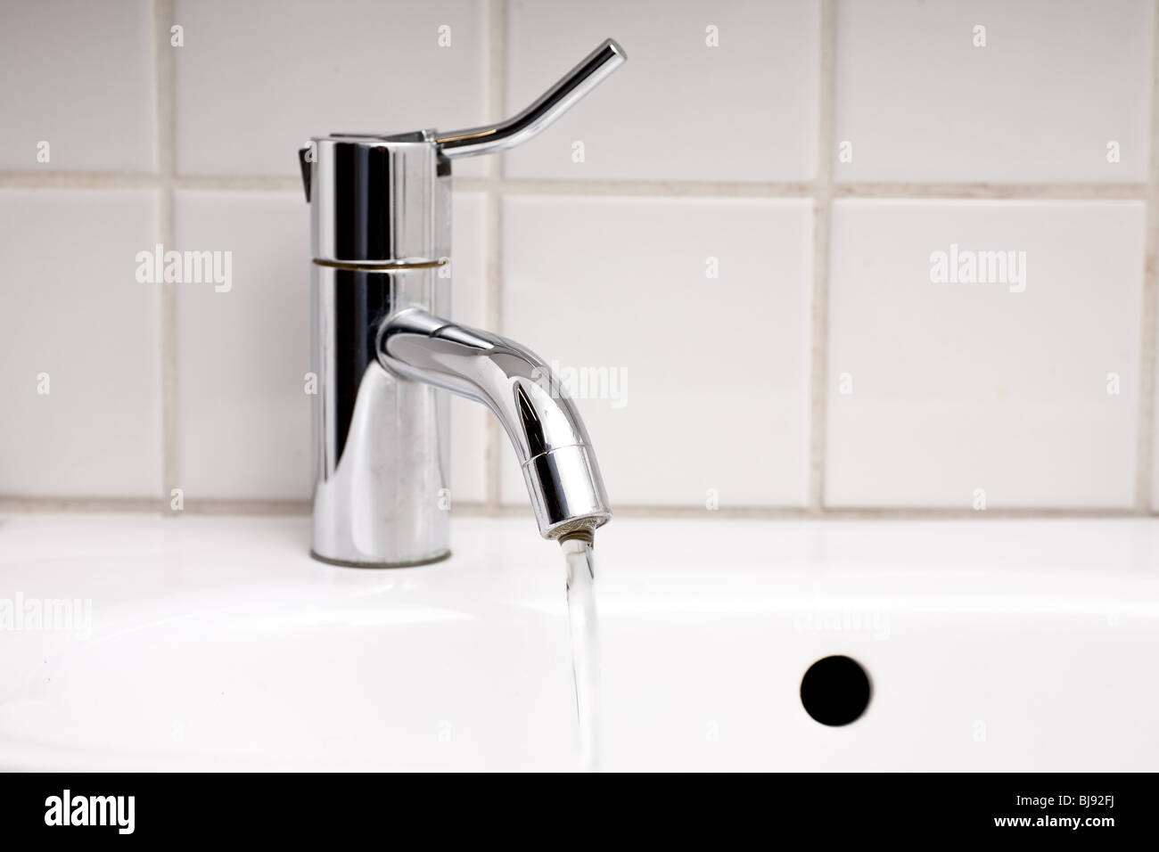 close up of sink and tap with running water in bathroom - Stock Image