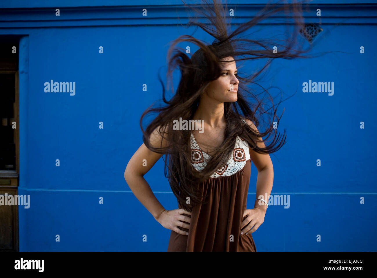 woman with wild, long, dark, straight, loose hair blowing in the wind - Stock Image