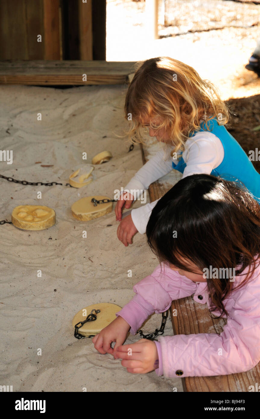 Children enjoy making footprints in the sand using wooden molds at the Naples zoo - Stock Image