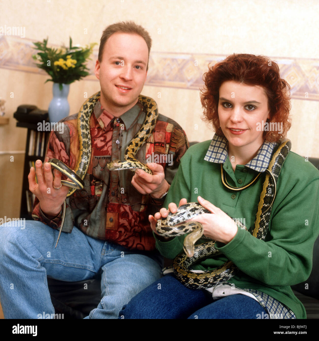 Couple holding snakes in hands sit on couch indoors  - SerieCVS500201b - Stock Image