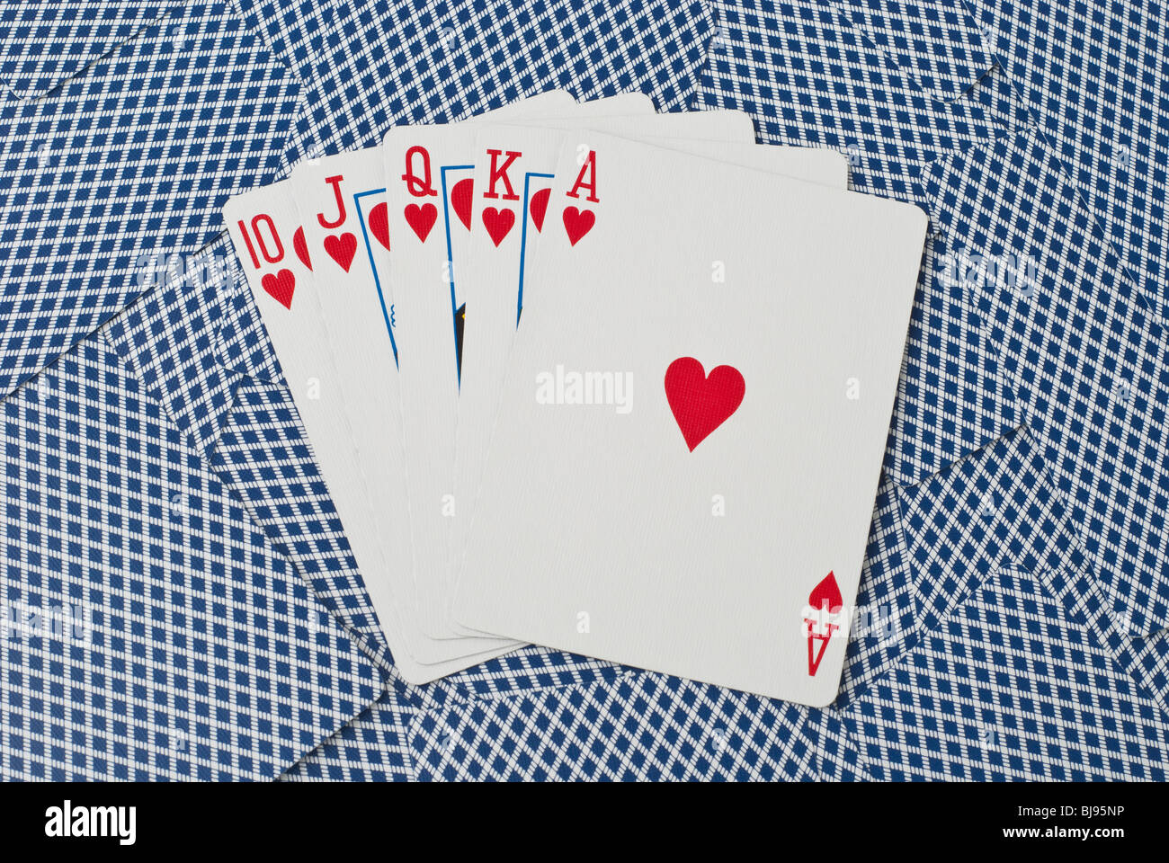 Five cards, showing a royal flush with hearts from ten to ace, on a background of backsides of blue playing cards - Stock Image