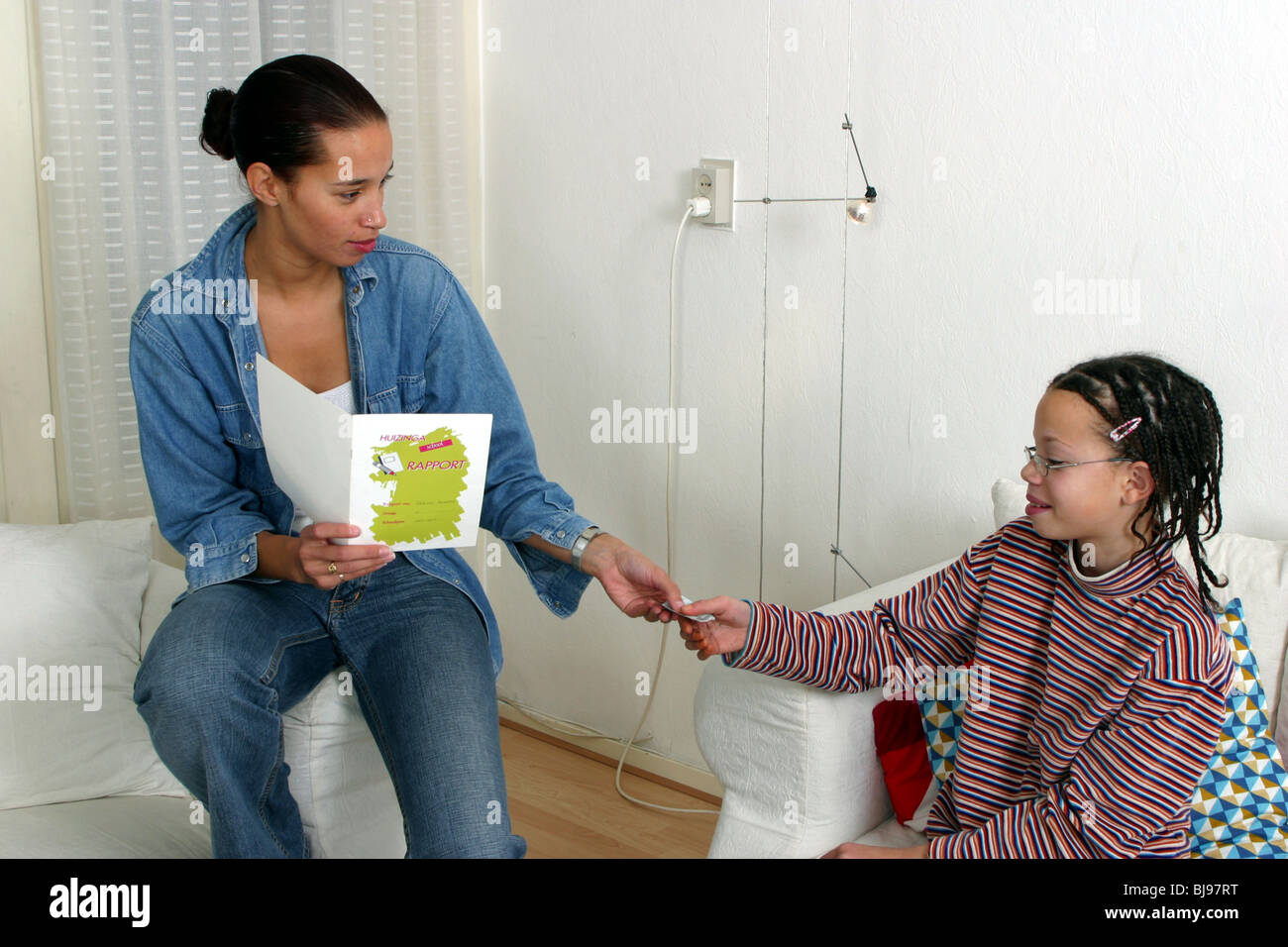 Child getting pocket money for good school report SerieCVS117007 - Stock Image