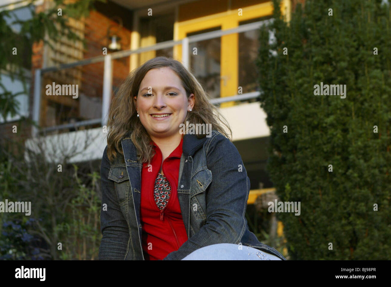 Happy portrait young woman sit in front of her new apartment and smile. - Stock Image