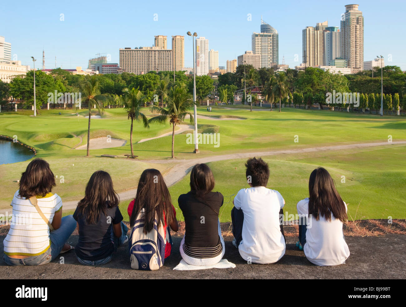 Young filipino's sitting on Intramuros wall looking over golf club to Manila; Intramuros; Manila; Philippines - Stock Image