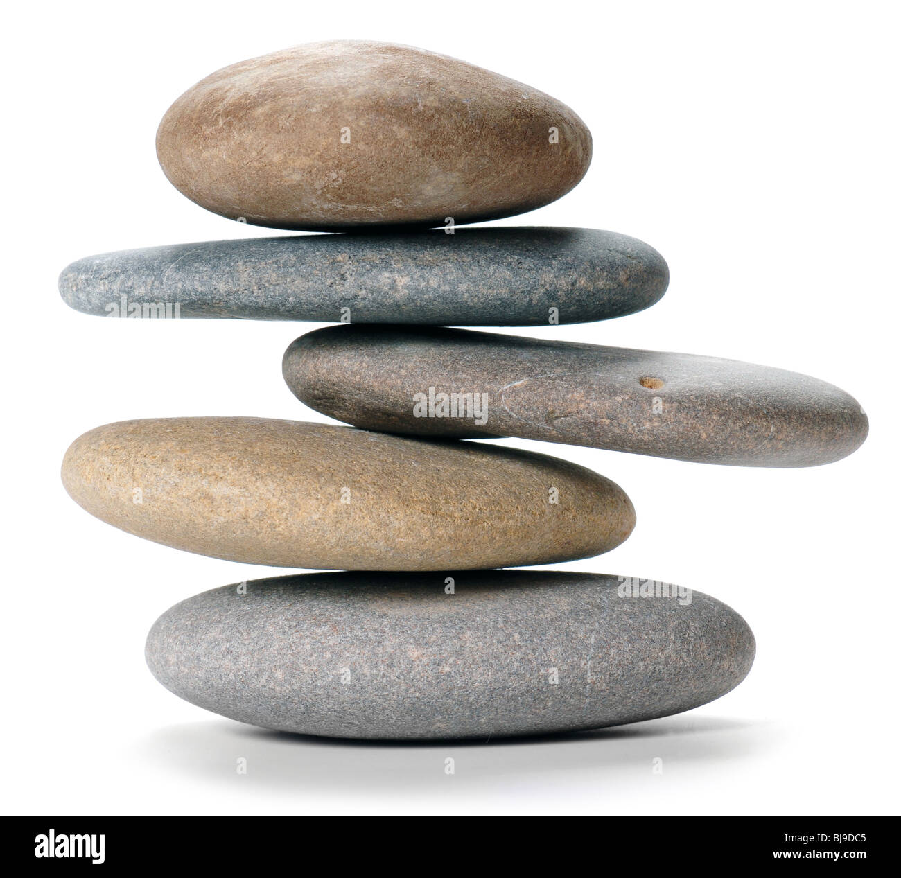 An isolated balanced stone tower on white background - Stock Image