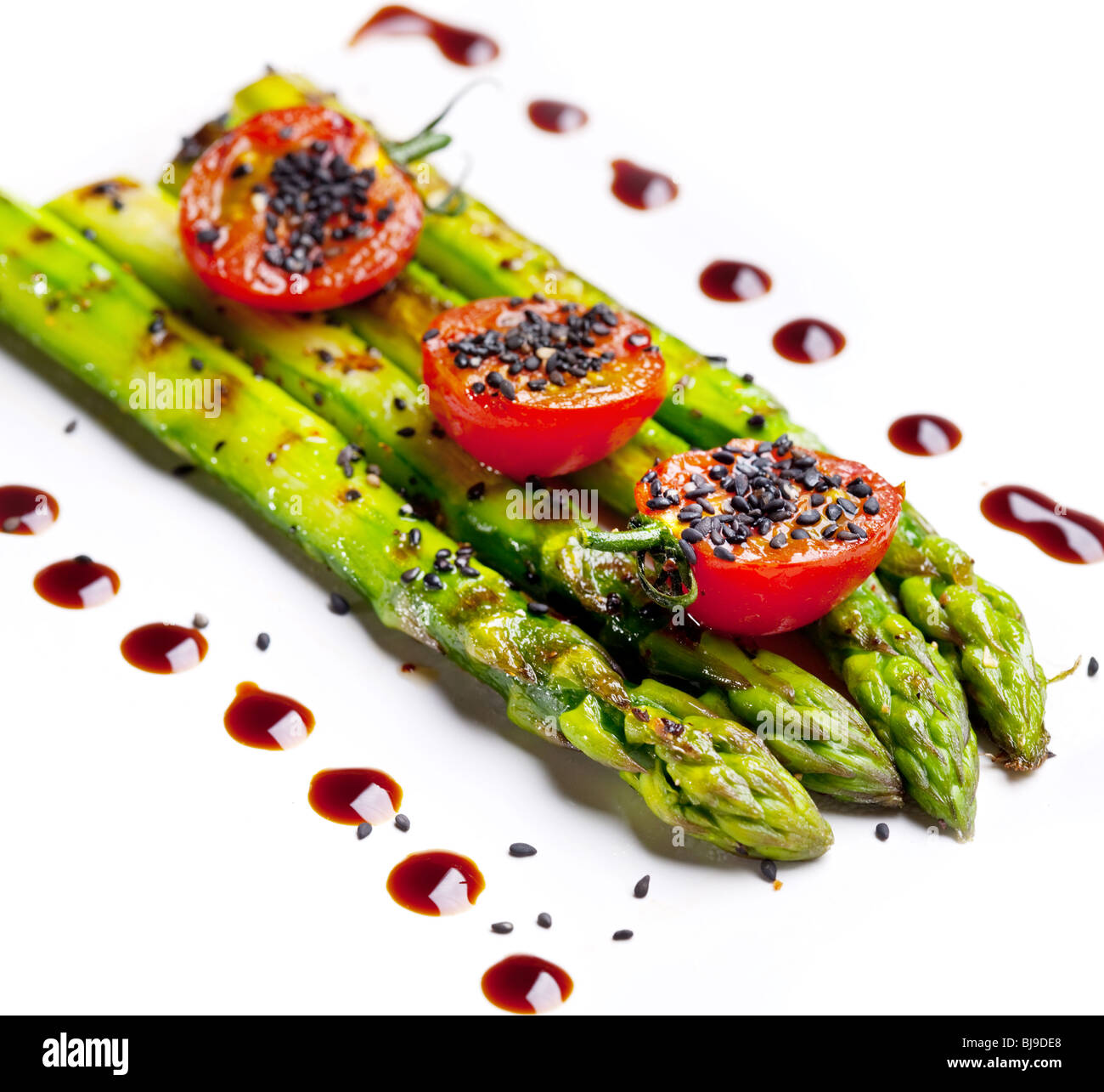 Fried green asparagus on a white background - Stock Image