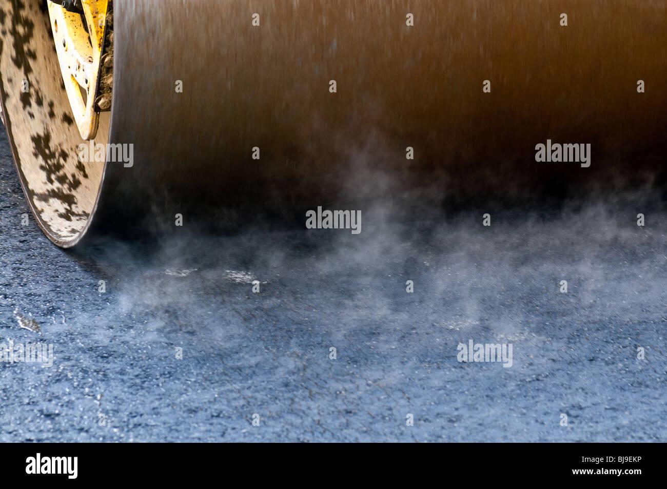 Making new road. Roller press fresh tar. Motion blur. - Stock Image