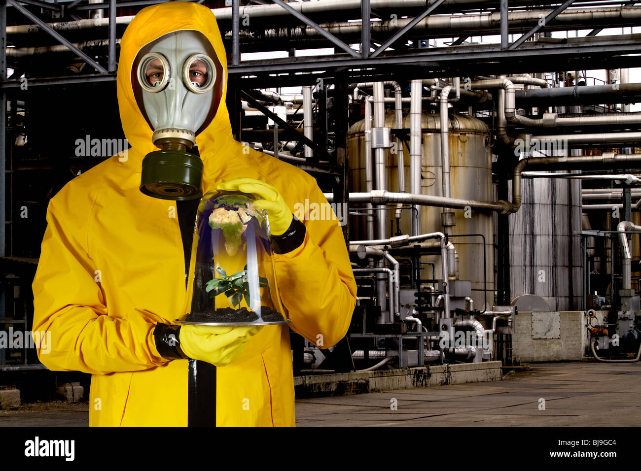 Man in chemical suit with mask holding plant in a portable greenhouse at chemical plant. - Stock Image