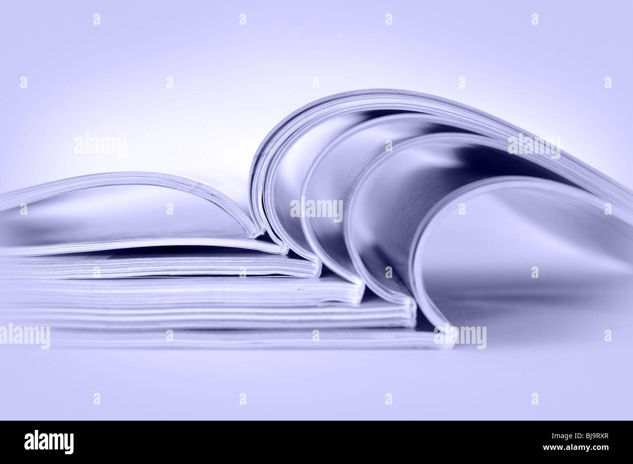 Stack of open magazines, toned blue - Stock Image