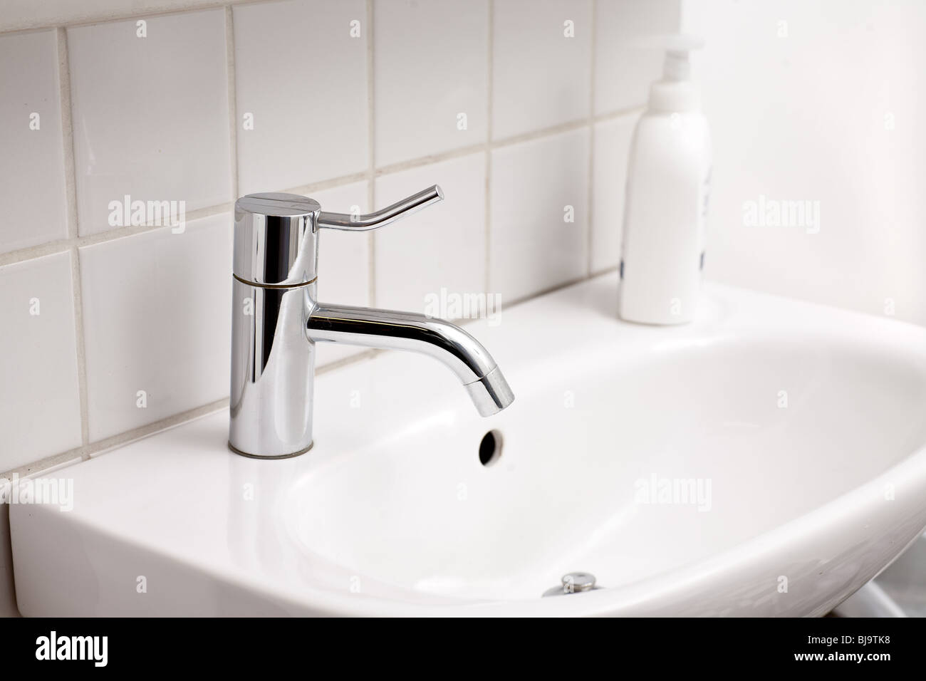 Close up of sink and tap in bathroom - Stock Image