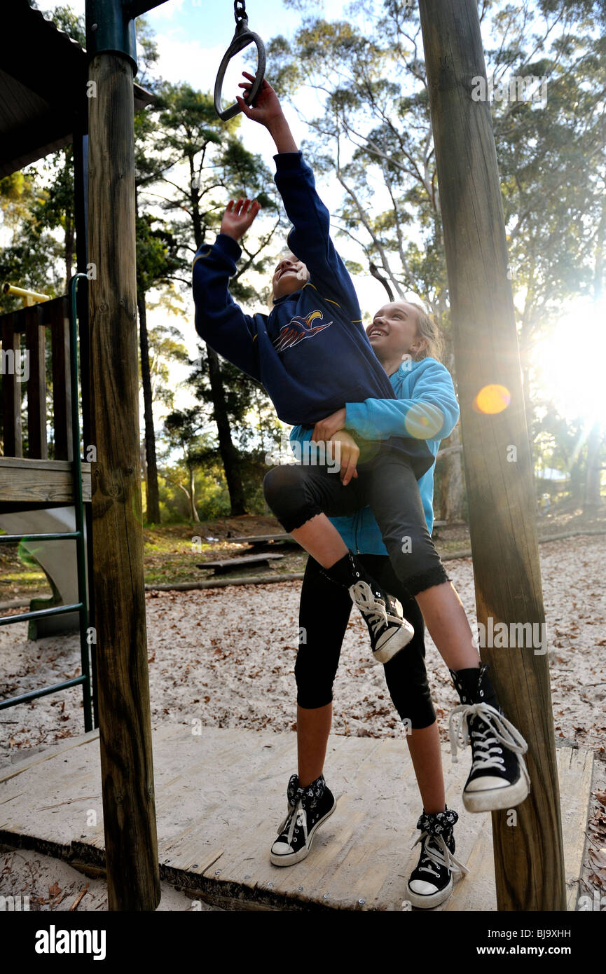 Young child (10 years old) helping younger sister (7 years old) reach a ring on outdoor playground. Stock Photo