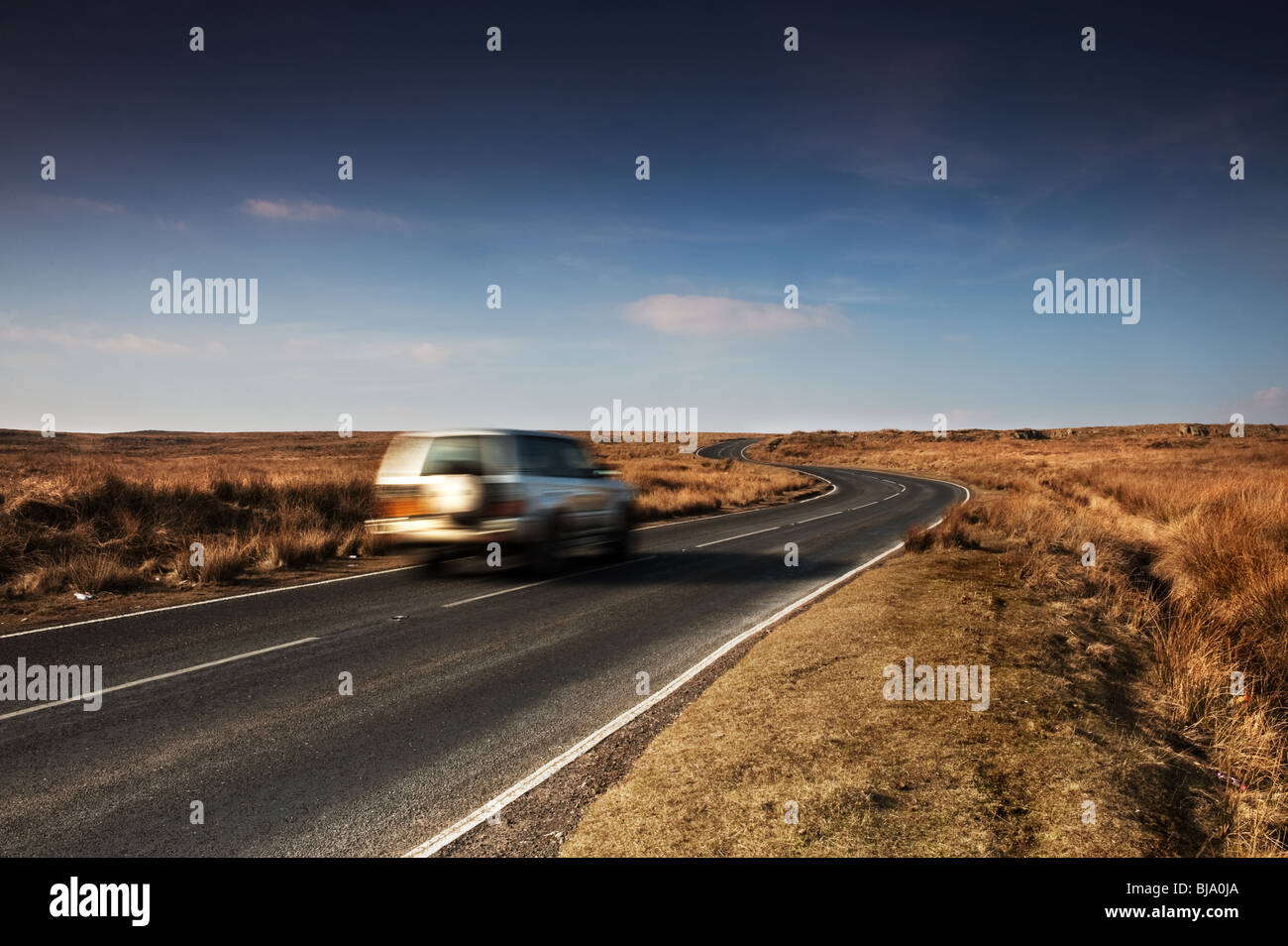A car speeding along the B4560 on Llangynidr Moors in South Wales. - Stock Image