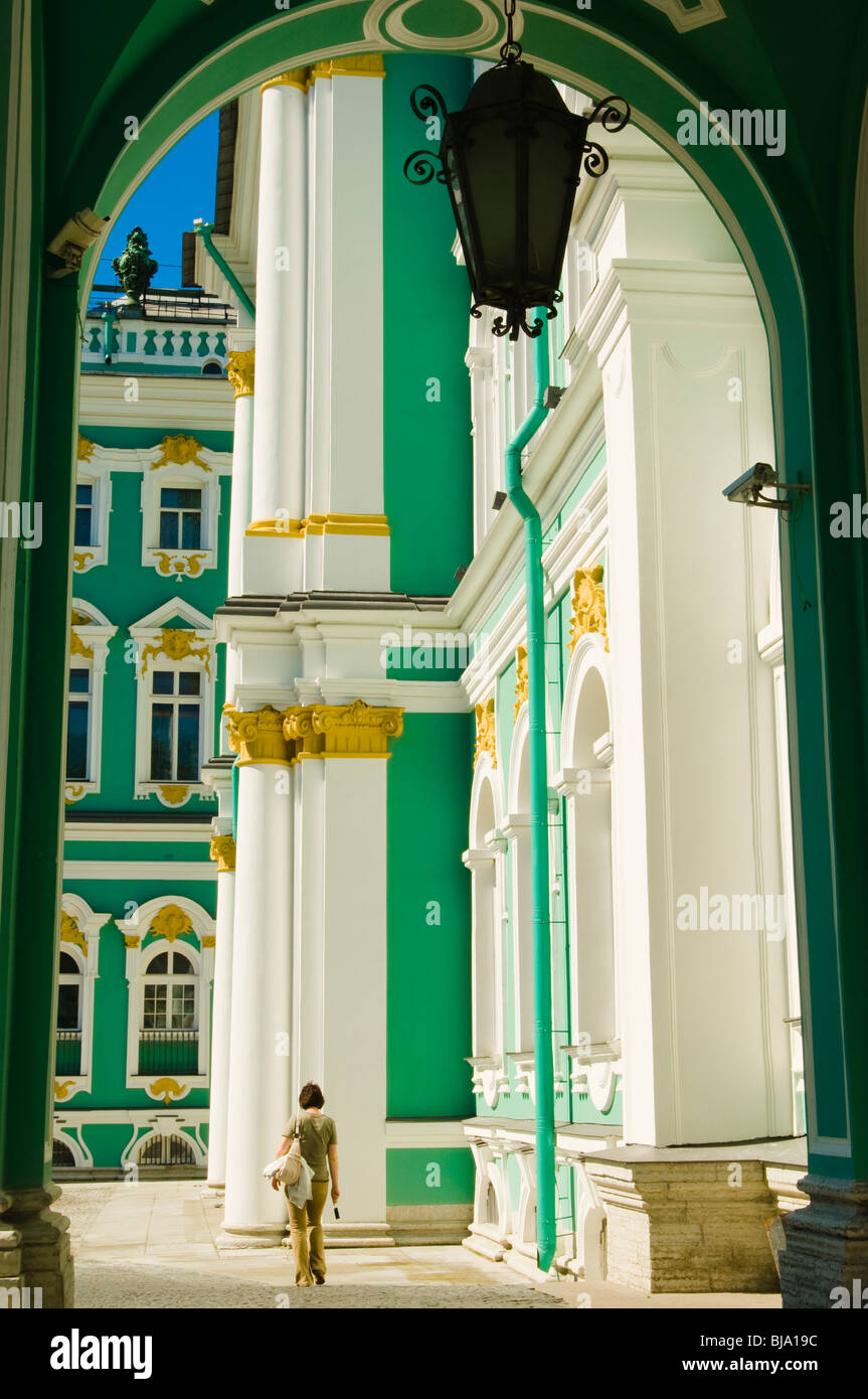 Woman walking past the Winter Palace, now part of the great Hermitage Museum, St Petersburg, Russia - Stock Image