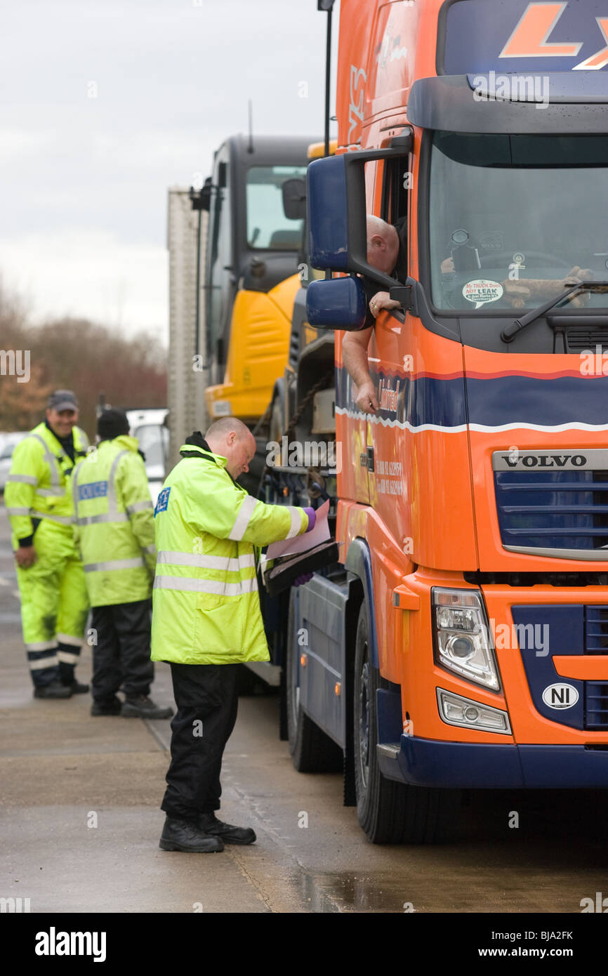 VOSA officers checking a lorry loaded with earth movers - Stock Image