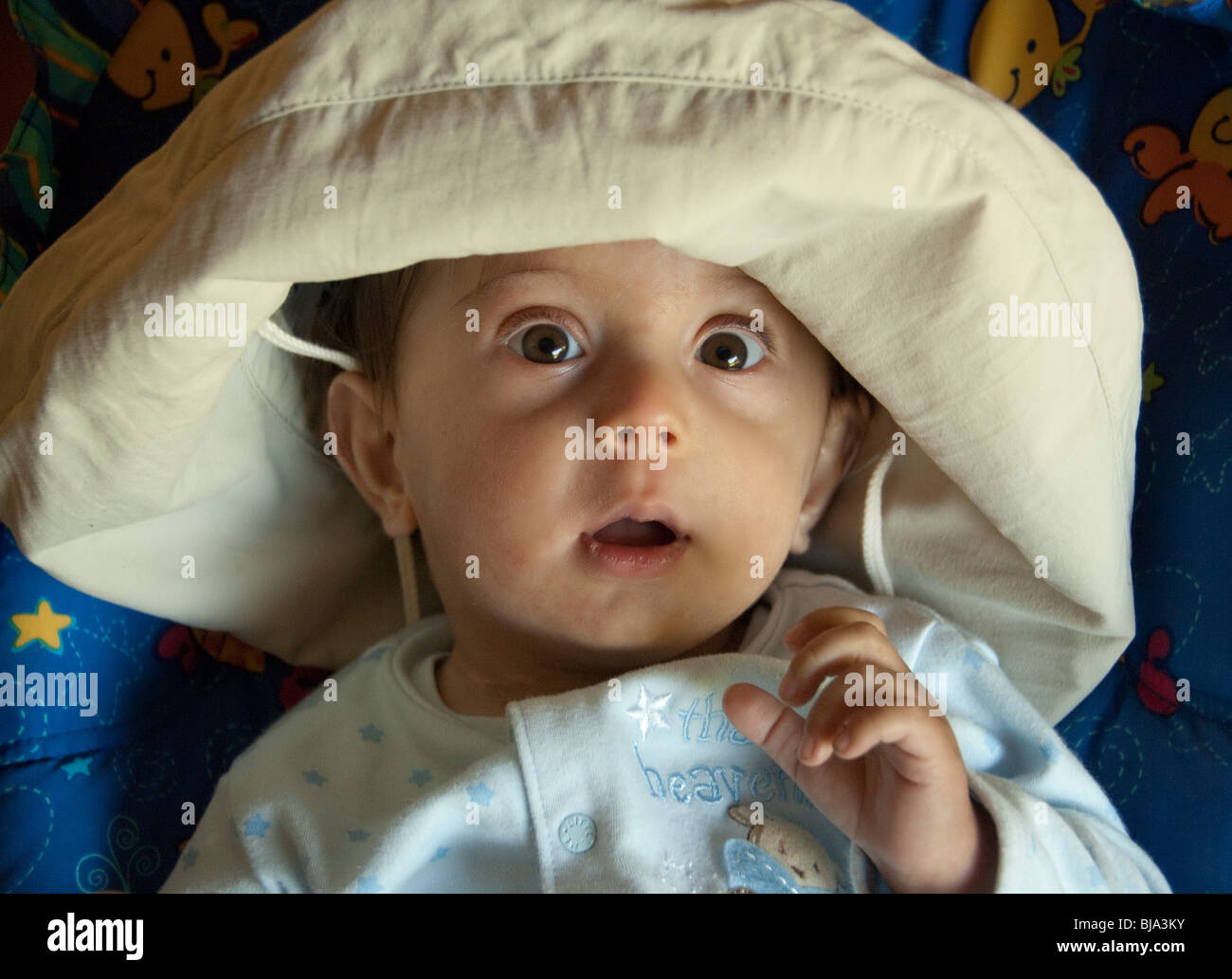 baby boy in mom's sun protection hat - Stock Image