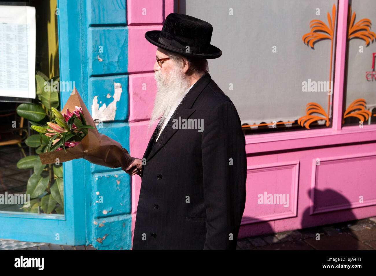 788e60ad senior orthodox jewish man with black hat and coat, carrying pink lilies  flowers past colourful pink and blue restaurant front
