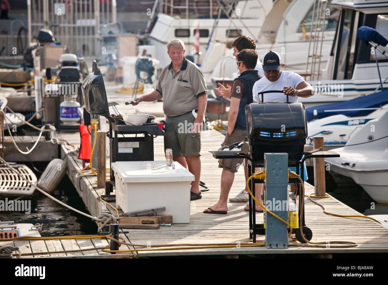 Men of mixed ages and races barbecuing at the Toronto waterfront - Stock Image