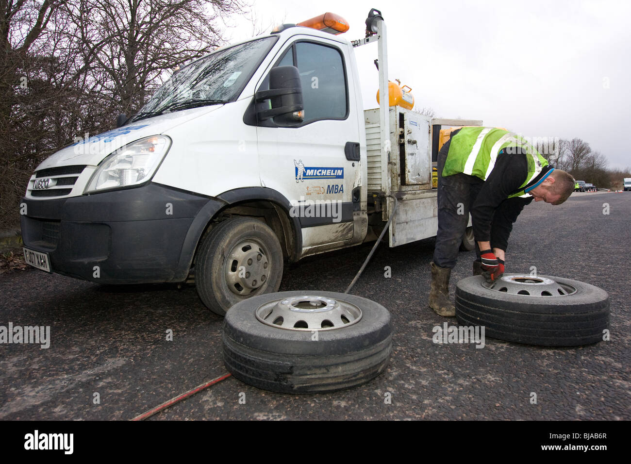 A Tyre Fitter working  on a lorry  wheel being changed at the roadside - Stock Image