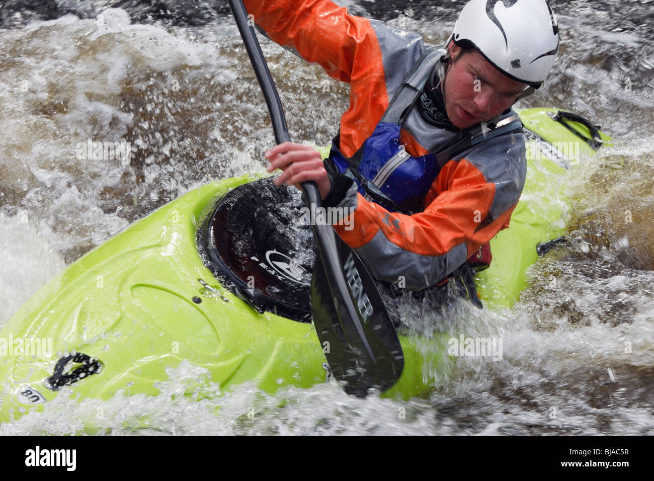 Kayaker kayaking in a kayak canoe in white water on Tryweryn River at the National Whitewater Centre, Frongoch, - Stock Image