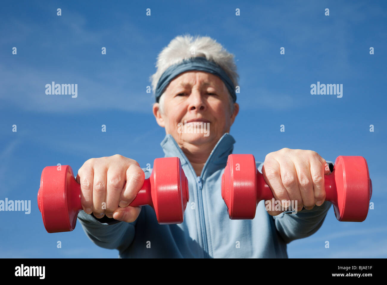 Active senior woman exercising with dumbbell hand weights somewhere outdoors to keep fit. Healthy lifestyle wellness - Stock Image