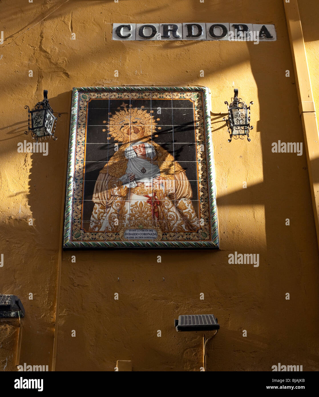 streetsign spelling out cordoba and tiled picture of religious icon on yellow wall in spain Stock Photo