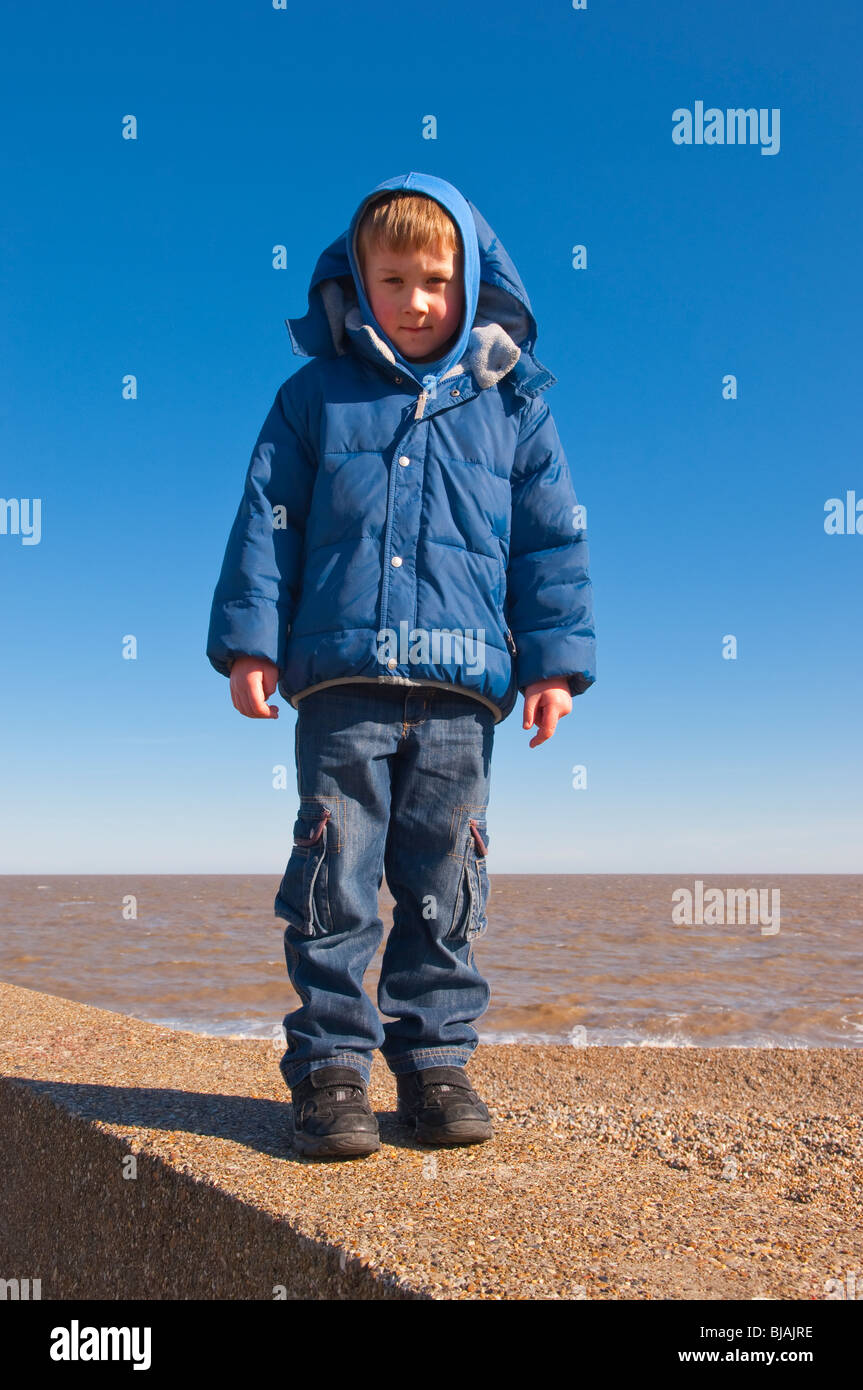 A MODEL RELEASED picture of a 6 year old boy standing on the sea wall on a uk beach - Stock Image