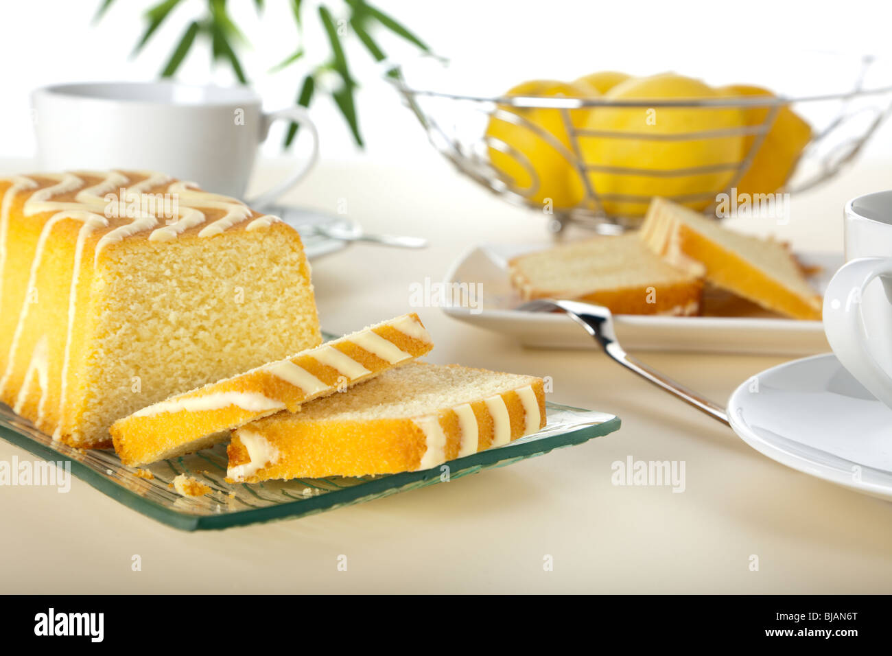 lemon cake and slices on coffee table - Stock Image