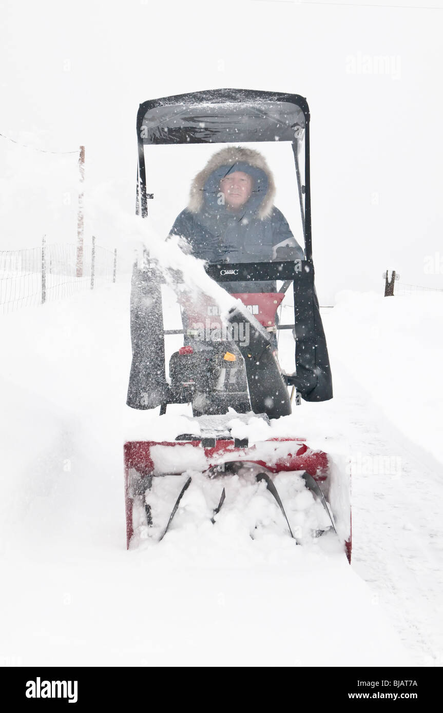 Man (male) using push Craftsman snow blower during heavy snow storm, Cocolalla, Idaho, USA - Stock Image
