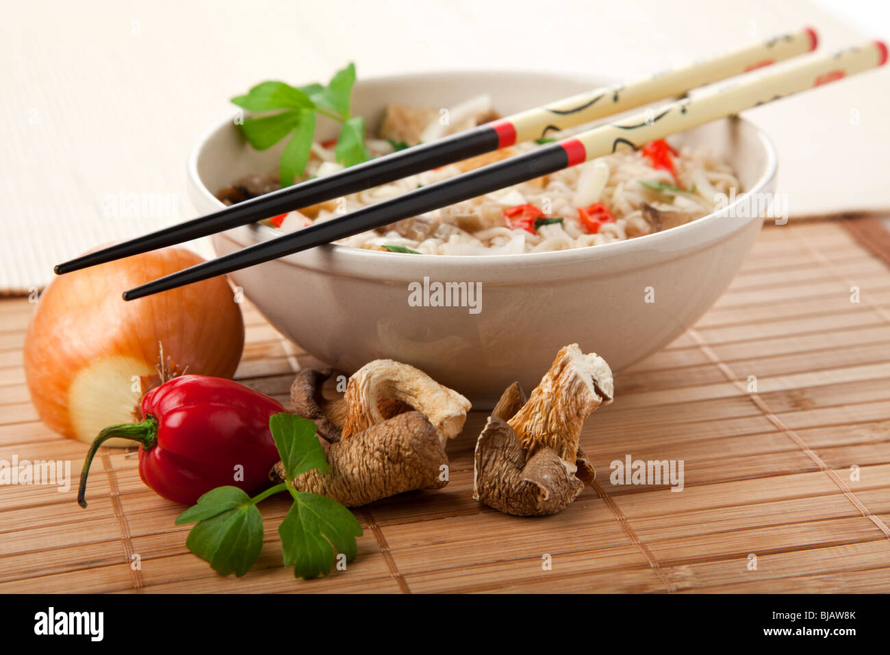 vegetarian ramen noodles dish, chopsticks at rest on bowl, ingredients in foreground - Stock Image
