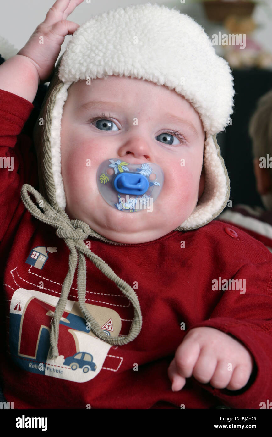 Baby boy wearing bonnet - Stock Image