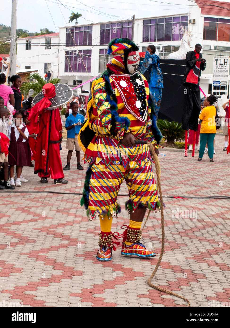Carnival character Jab Jab wielding a plaited hemp whip with Moko Jumbie in the background, Kiddies carnival Tobago - Stock Image